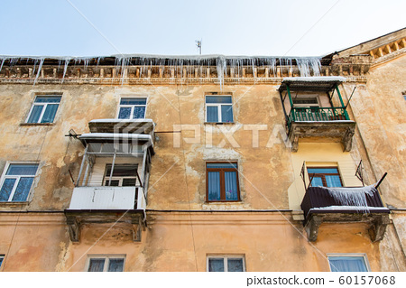 Icicles hang from roof of building. Danger for passers, threat of death and injury from icicles. Theme the winter risks 60157068