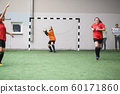 Young active sportswoman going to throw soccer ball to other player of her team 60171860