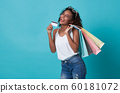 happy woman showing credit card and shopping bag 60181072