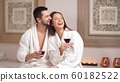 Happy charming couple drinking wine and laughing in modern wellness salon 60182522