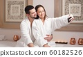 Beautiful young couple makes a selfie in modern wellness salon 60182526