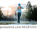 Woman having a city walk in thawing snow 60187203