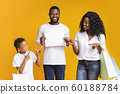 Joyful family pointing at white advertisement board and holding shopping bags 60188784