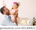 Happy daughter in crown playing with father 60188822