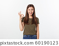 Happy young woman showing ok sign with fingers an winking isolated on a gray background. 60190123