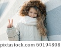 Close-up outdoor winter portrait of child, blonde girl with curly hair of 7, 8 years in fur hood, girl smiling showing victory sign 60194808