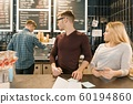 Young people working in coffee shop, man and woman near bar counter, receiving order by phone, barista on the background of coffee machine. Teamwork, staff, small business, people concept 60194860