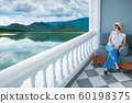 Women in white shirts, pants, weave hats looking at the beautiful view from  the balcony. 60198375