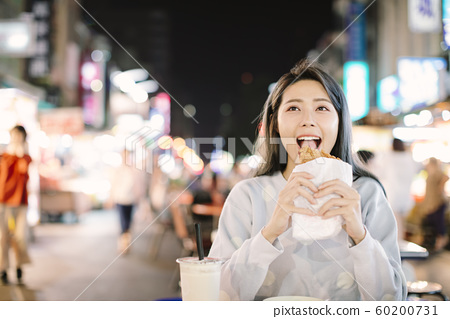 Asian woman enjoy  Chicken Fillet with street food 60200731