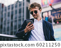 A Young Guy With Blonde Hair In Sunglasses Looks At His Mobile Phone While Being Outdoors On A Summer Day 60211250