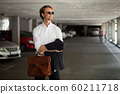 Young business worker in sunglasses stands in the parking lot 60211718