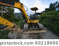 The modern excavator on the construction site with sunset sky. Large tracked excavator standing on a hill with a green grass. Machinery for a construction of a new building in the countryside. 60218666