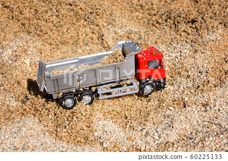 Children's toy truck on sand near sea.  60225133