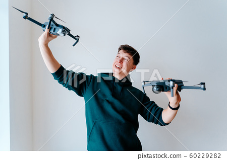 Guy holds two quadrocopters against a wall 60229282
