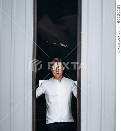 A handsome guy in sunglasses opens the door to the hangar. 60229285