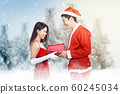 Asian man in Santa costume giving his girlfriend a gift box  60245034