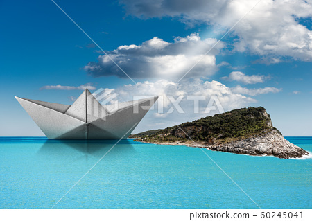 Paper boat in the turquoise sea with island and sky with clouds 60245041
