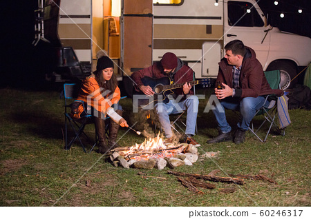 Man playing on guitar around camp fire while his friends ar roasting marshmallows 60246317