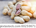 Roasted peanuts on a wooden bowl and sack 60250671