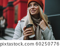 Young lady with smiling face and coffee in hands 60250776