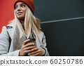 Young lady with coffee to go in hands 60250786