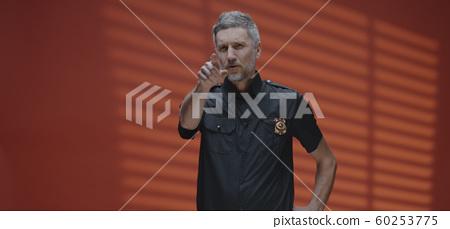 Stern policeman talking to camera 60253775