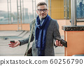 Confused handsome man holding cellphone and wallet 60256790