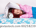 Annoyed girl covering her ears with a pillow from the alarm clock 60258239
