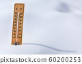 Wooden thermometer standing in the snow, sun 60260253