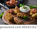 Spiral cut small potatoes on skewers baked with olive oil and served with herb curd and bacon strips 60262162