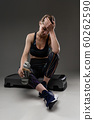 Sport woman sits with bottle of water after training and relax 60262590