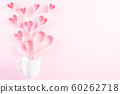 Pink paper hearts splash out from white coffee cup 60262718