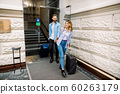 Pretty woman and handsome man holding hands are leaving a hotel with their suitcases 60263179