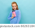 portrait of a european girl drinking holding a glass on a light blue background 60263184
