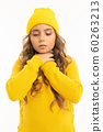 European attractive girl in a yellow hat and jacket holds hands near the throat on a white studio 60263213