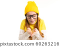 cute european red-haired girl in glasses holds lenses on a white studio wall 60263216
