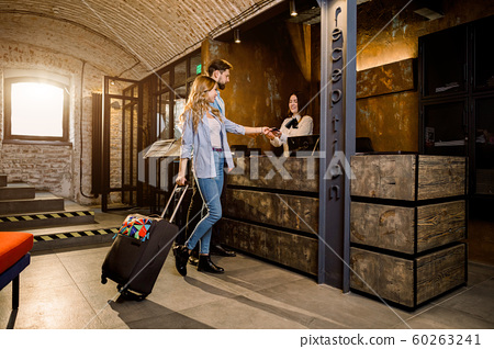 Couple on a business trip doing check-in at the hotel. Young couple near reception desk in hotel 60263241