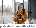 Dark-haired young cute reporter watching photos in camera 60274041