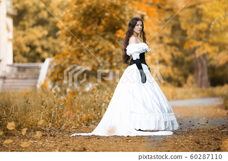 Woman in a white Victorian dress in an autumn park 60287110