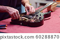 Guitar maker change strings of electric guitar 60288870