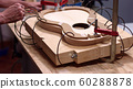 Guitar maker clamp together the acoustic guitar structure 60288878