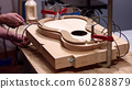 Luthier uses springs to clamp guitar body 60288879