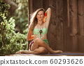 Yoga asana by young beautiful woman near wooden house in the tropical paradise with palms and banana trees on Zanzibar island 60293626