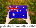 Box with Australia flag in female hands. Fir 60295069