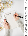 Female hands writing My Goals in a notebook. 60295085