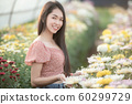 Beautiful young woman traveler looking flowers field  60299729