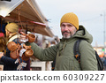 Man selecting gifts on the Christmas market in 60309227