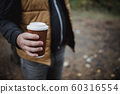 A man holds a takeaway cardboard glass with tea 60316554