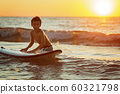 boy surfer getting ready for ride on the ocean wave against beautifull sinset light 60321798