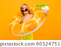 portrait of a fun european blond boy in yellow swimming trunks and sunglasses with a swimming circle 60324751